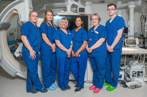 Cardiology team at a Manchester or Cheshire private hospital smile in front of cardiac equipment.